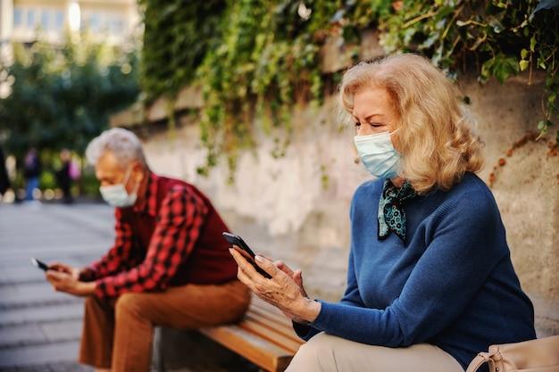 外のベンチに座って携帯電話を使用して保護マスクを着用した金髪の年配の女性。