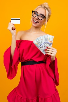 Blond sexy girl in a red dress with bare shoulders holds a bunch of loan money and a credit card credit mockup on an isolated wall