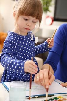 Blond smiling little girl hold in arm brush