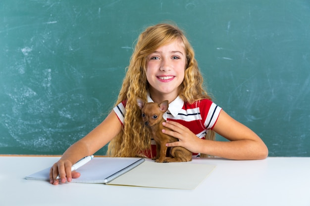 Blond student girl with puppy dog at class board