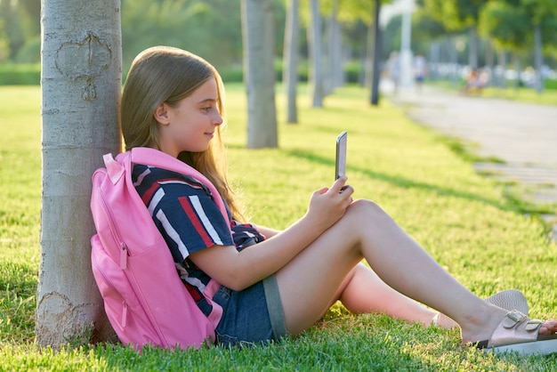 Blond student kid girl with smartphone in park