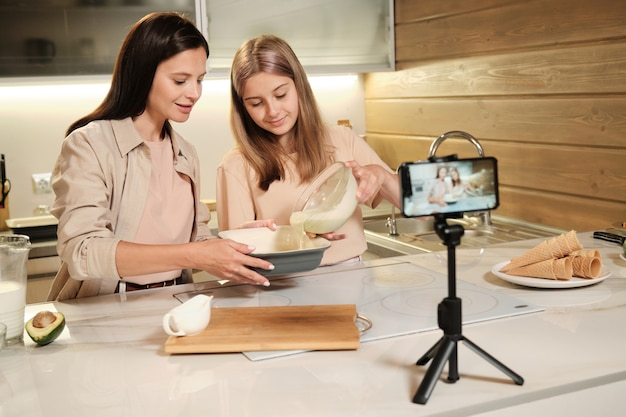 Blond teenage girl pouring mixture of homemade icecream ingredients into large bowl in front of smartphone camera in the kitchen