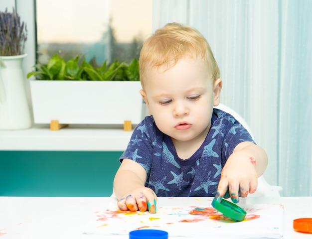 Белокурая малышка рисует руками на бумаге дома