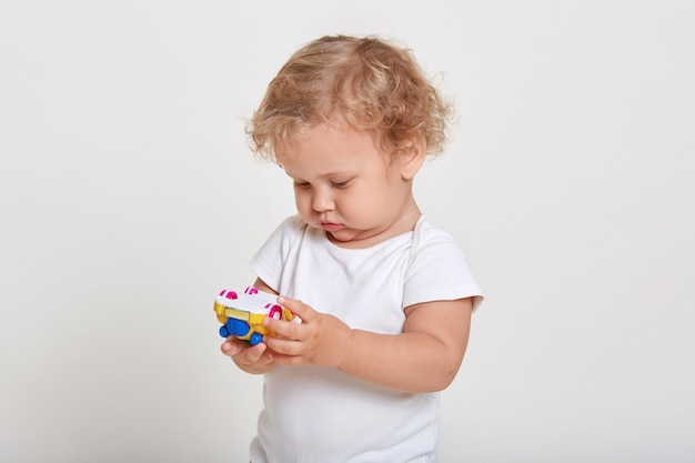 Blond toddlers playing with color car isolated on white space, looking concentrated at toy in his hands