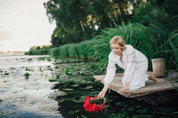 ブロンドのウクライナの女の子が水に向かって曲がる