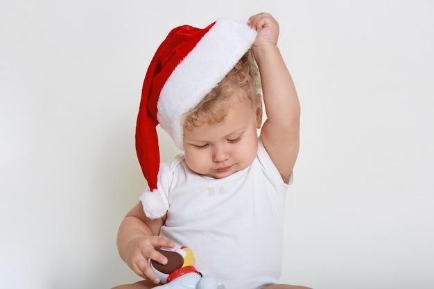 Светловолосый волнистый мальчик в боди, держащий пластиковую игрушку и снимающий шляпу санта-клауса с головы, смотрит вниз, позирует изолированно над белой стеной, развлекается с любимой игрушкой.