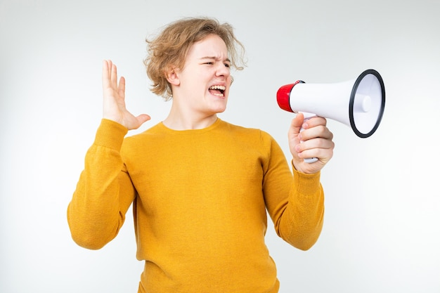 Blond wavy man shouting news in a megaphone on a white studio background.