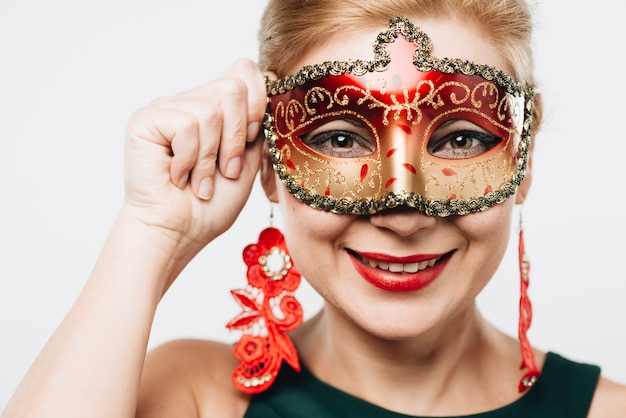 Blond woman in bright red carnival mask