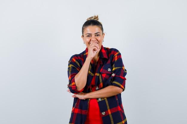 Donna bionda in camicia a scacchi con la mano sulla bocca e guardando felice, vista frontale.