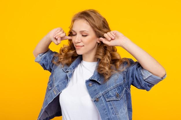 一人でスタジオに立って耳を閉じる金髪の女性。