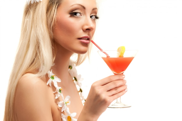 Blond woman in costume made from chamomile flowers holding cocktail in glass