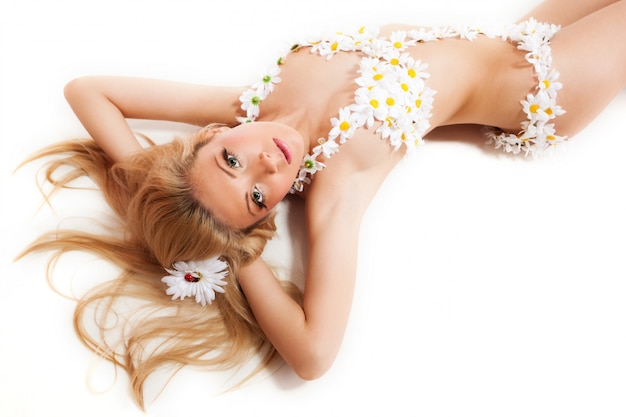 Blond woman in costume made from chamomiles lying on white floor
