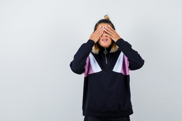 Blond woman covering eyes with hands in black tracksuit and looking wistful
