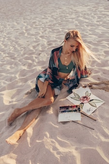 Blond woman drawing watercolor flower by brush on the beach