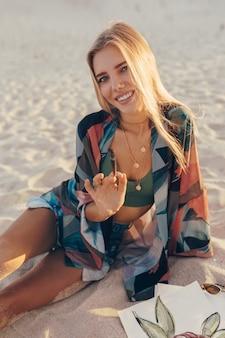 金髪の女性がビーチでブラシで水彩花を描く
