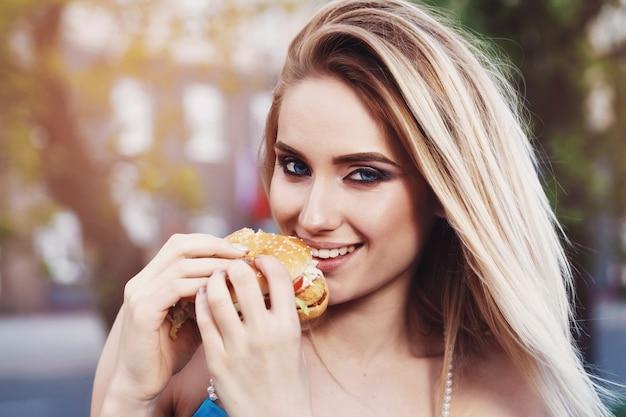 晴れた夜に屋外でおいしいハンバーガーを食べる金髪の女性