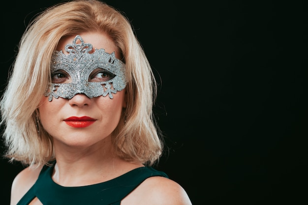 Blond woman in grey carnival mask