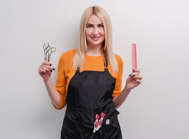笑顔と彼女の手でプロのはさみと白い表面で隔離の櫛を保持している金髪の女性美容師
