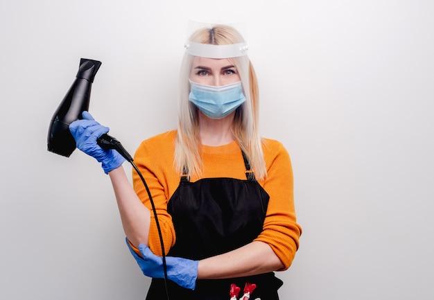 薬のマスクと手袋を着用した金髪の女性美容師