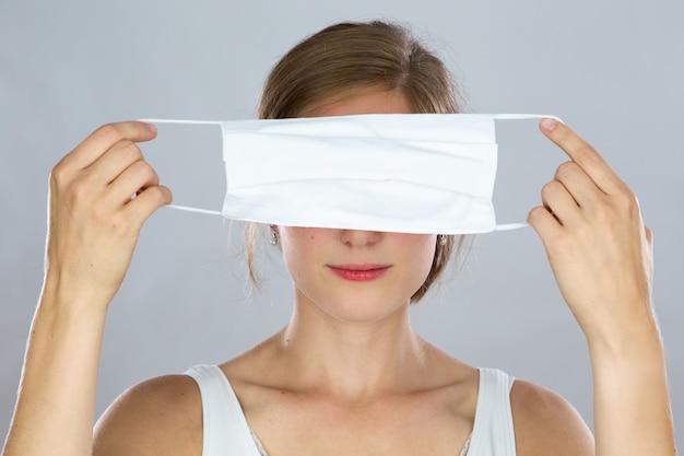 그녀의 머리 앞에서 그녀의 눈을 덮고 얼굴 마스크를 들고 금발 여자