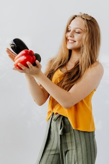 Blond woman holding fruit and vegetables