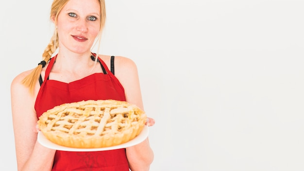 Blond woman holding plate with apple pie