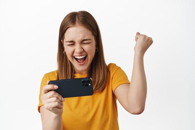 Donna bionda che tiene lo smartphone in orizzontale, gioca al videogioco mobile e alla pompa del pugno urla di gioia e successo, celebra la vittoria, muro bianco