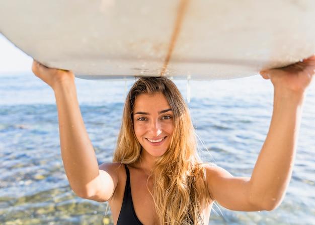 Blond woman holding surfboard on head