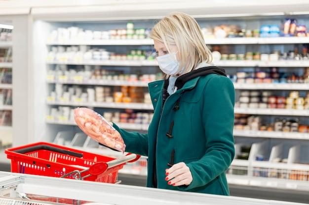 マスクで金髪の女性は冷凍食品部門のスーパーで買い物をしています。コロナウイルスのパンデミック時の検疫。