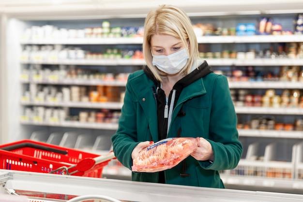 医療マスクの金髪女性がスーパーで買い物をしています。パンデミックにおける自己隔離。