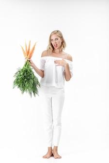 白い背景に緑の葉とニンジンを保持している白いブラウスのブロンドの女性。女の子はニンジンとダイエットで気分が悪い