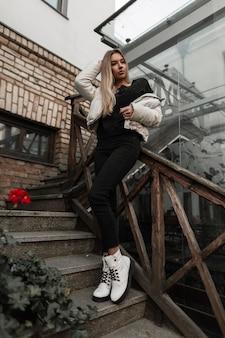 黒のスタイリッシュなジーンズの白いジャケットを着た金髪の女性は、石のヴィンテージの階段で休んでいます