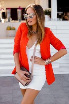 屋外でポーズをとる完全な唇を持つ大きなサングラスのブロンドの女性。赤いジャケット、スタイリッシュなシルバーのアクセサリー。完璧な姿。