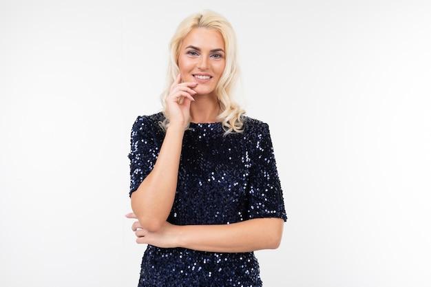 エレガントな青い光沢のあるドレスを着た金髪の女性は物思いにふける表情をします