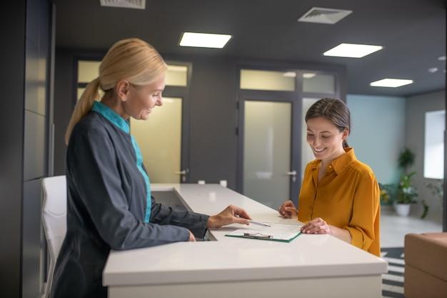 Блондинка женщина в сером пиджаке разговаривает с посетительницей