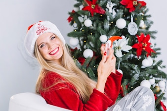 Blond woman in Santa hat sitting with phone