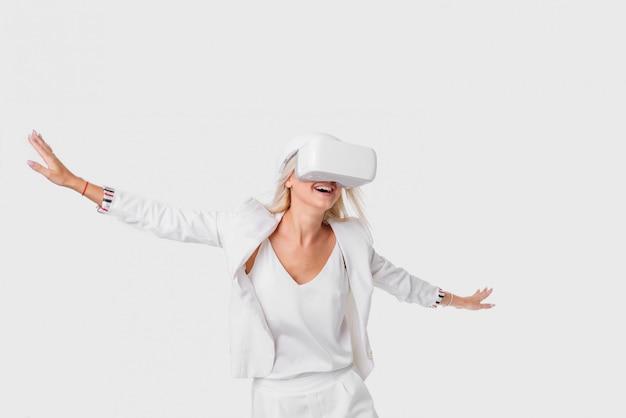 仮想現実ゴーグル付きの白いスイートのブロンドの女性。ホワイトスペースで撮影スタジオ