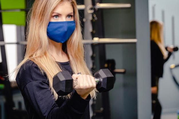 금발 여자는 유행병 동안 체육관에서 훈련입니다. 소녀는 의료 마스크에서 운동을합니다. 코로나 바이러스 기간 동안 체육관. 코로나 바이러스, 질병, 감염 개념.