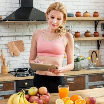 Blond woman in the kitchen with fruits