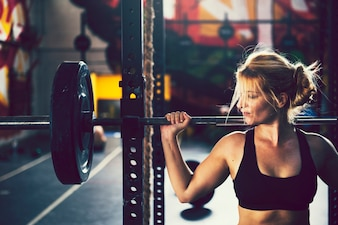 Blond woman lifting weights gym