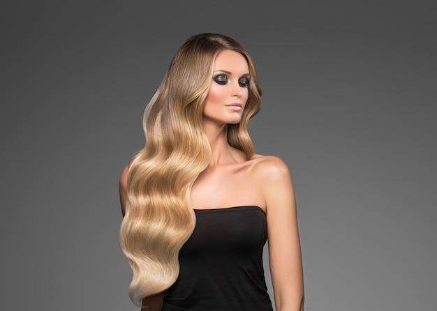 Белокурая женщина длинные волосы вьющиеся естественный модный макияж. студийный снимок.