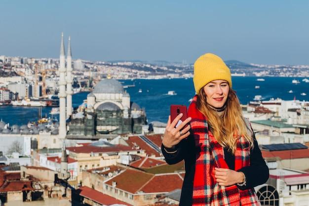 Белокурая женщина делает фото на телефон на крыше гранд базар, стамбул, турция. девушка в желтой шляпе принимает selfie в солнечный осенний день. путешественник девушка гуляет по зимнему стамбулу. Premium Фотографии