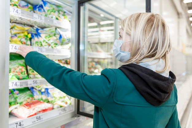 Blond woman in medical mask chooses frozen food in a supermarket. precautions during the coronavirus pandemic.