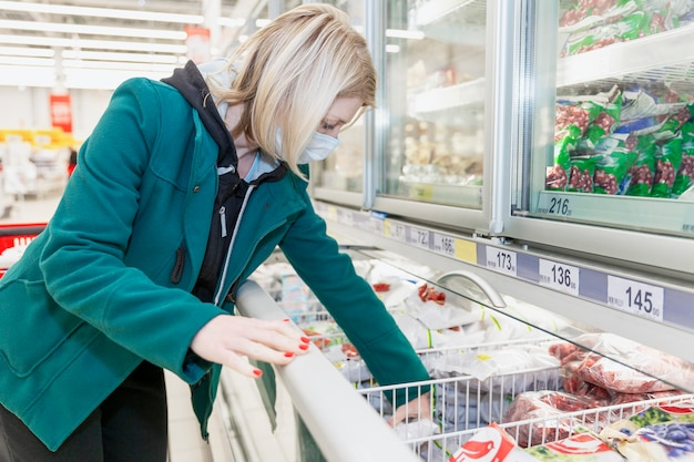 A blond woman in a medical mask chooses products in the freezing department in a supermarket. precautions during the coronavirus pandemic.