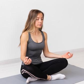 Блондинка женщина медитирует на коврике для йоги