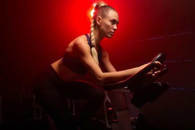 煙のような空間でジムで運動し、トレーニングに集中している自転車の金髪の女性