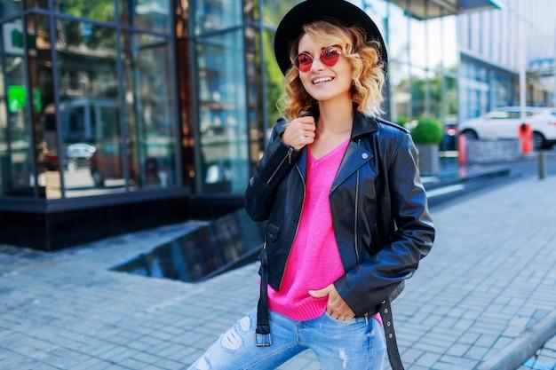 金髪の女性が近代的な通りでポーズします。スタイリッシュな秋の服、革のジャケット、ニットのセーター。ピンクのサングラス。