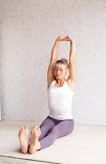 Блондинка женщина упражнениями йоги дома растяжения