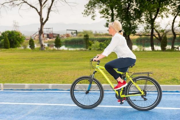 静かな湖や川を自転車に乗って、アクティブなライフスタイルを概念化したクローズアップの側面図で反射する金髪の女性