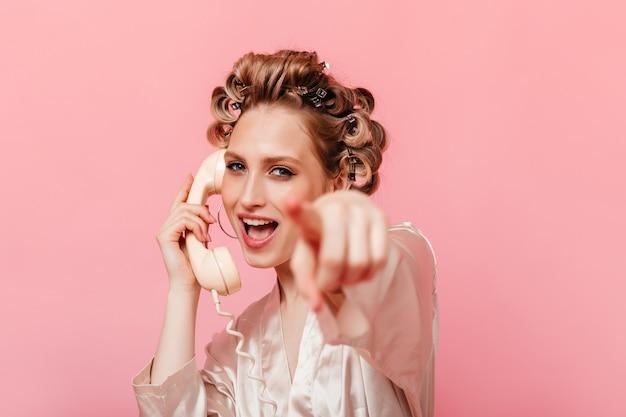 La donna bionda in abito di seta a casa sta parlando al telefono e punta il dito davanti contro il muro isolato